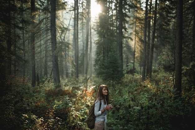 森の中のマグカップを保持している内気な少女