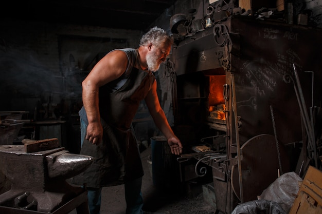 Кузнец в фартуке работает в кузнечной мастерской