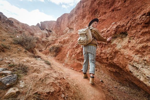 うさぎ、帽子、野生の砂の間で行くバックパックの美しい少女