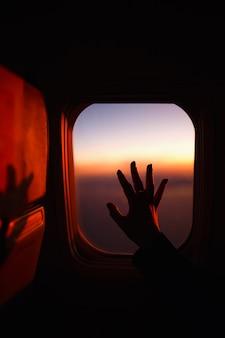 飛行機の窓を渡った手。旅行の概念。