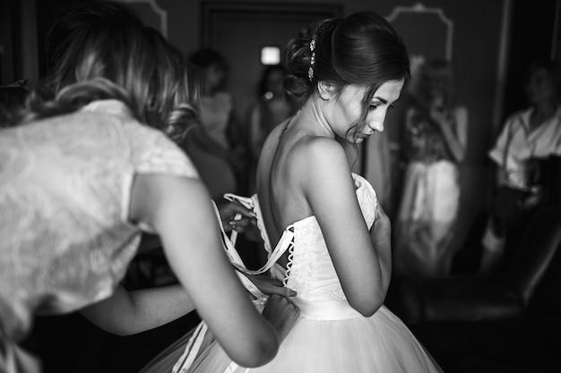 黒と白の写真。花嫁はウェディングドレスを着る。