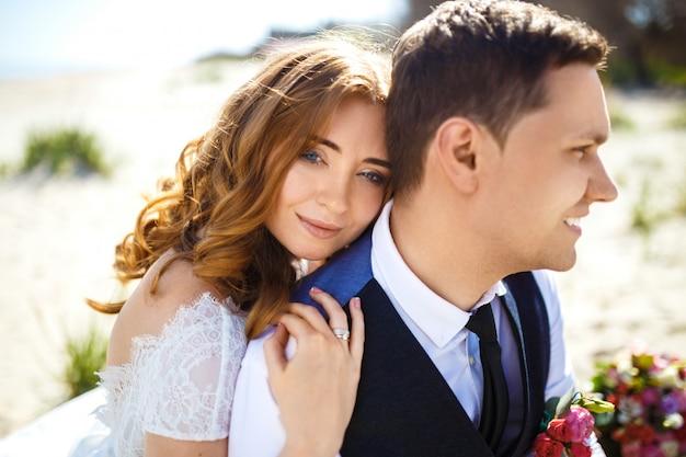 美しい花嫁と花婿は、ビーチを歩いてお互いを楽しんでいます。彼らの結婚を祝う幸せなロマンチックな若いカップル
