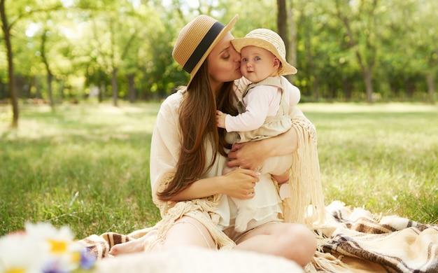 Счастливая стильная и любящая семья. мать, играя со своим ребенком на открытом воздухе. милый ребенок улыбается и наслаждается. день матери концепция