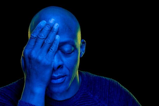 黒の背景に分離された青い光で絶望的な黒人男性のスタジオ撮影