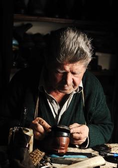 老人、靴屋、彼の工房で古い手作りの靴を修復する