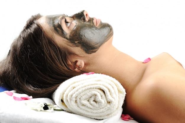 女性の顔にシーマッドマスク。スパ