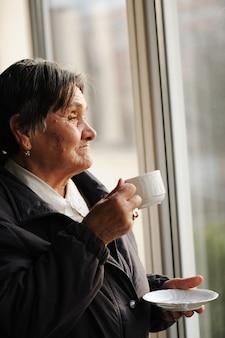Портрет старшей женщины, глядя через окно и выпить чашку кофе