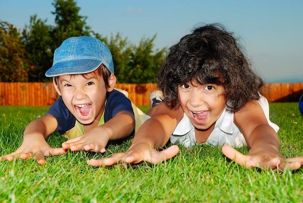 美しい緑の牧草地で幸せな子供たち