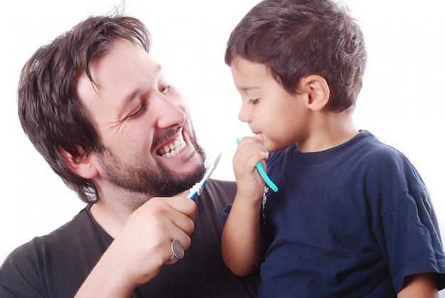 Отец учит своего сына, как чистить зубы
