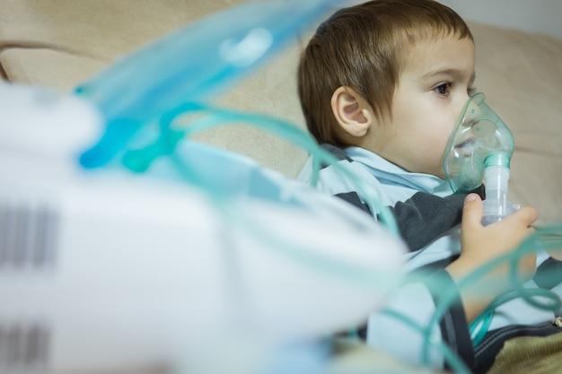 吸入器のマスクで美しい病気の少年の吸入療法。