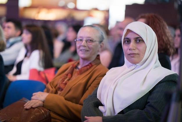 Мусульманская женщина с хиджабом и матерью в аудитории