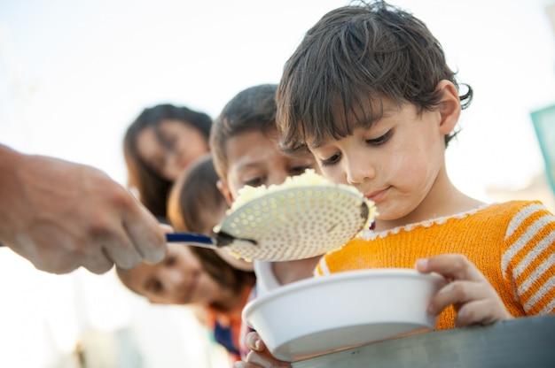 空腹の子供たちが慈善事業で養われている