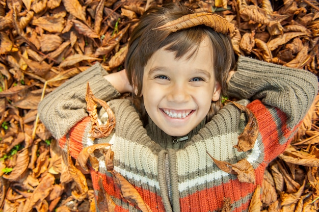 乾燥した葉の上に横たわる少年