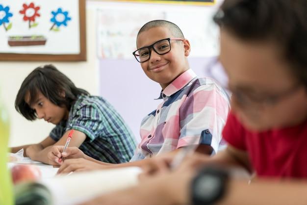 Юные мальчики начальной школы, пишущие экзамен в классе