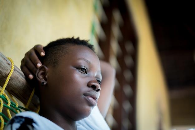 Красивая молодая черная женщина, сидя перед домом