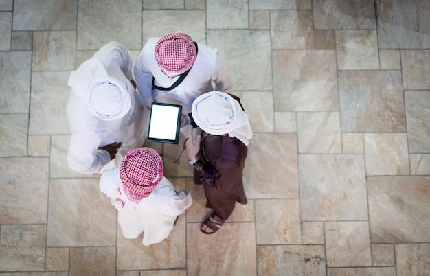 タブレットで若いアラブのビジネスマンのグループ