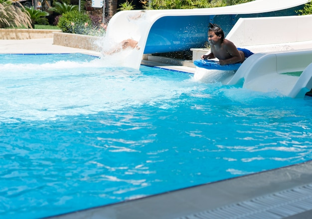 プールでプールのウォータースライドを楽しむ子供たち