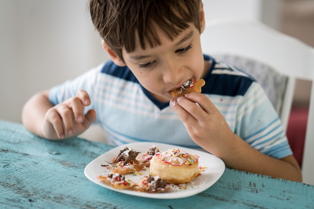 Маленький мальчик ест вкусный пончик