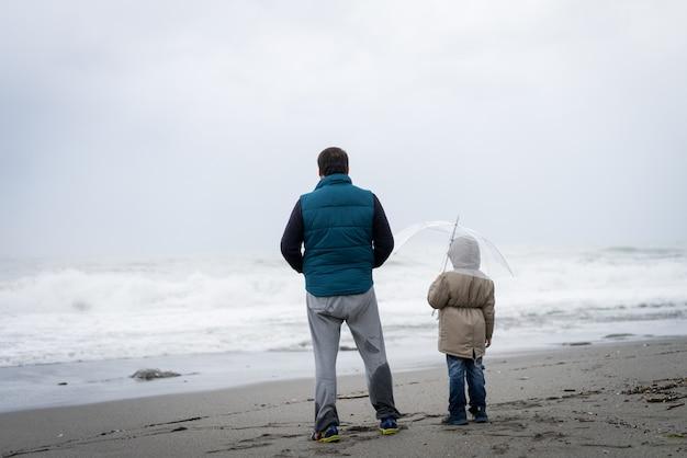 父と息子の冬のビーチで楽しんで