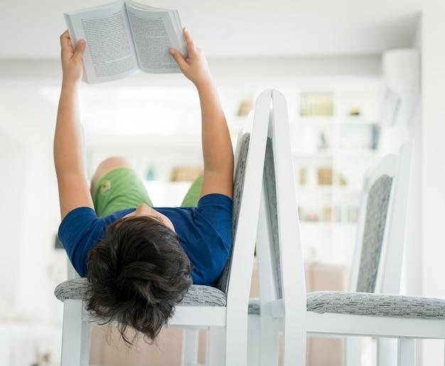 家で本を読んでいる少年