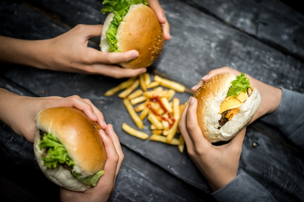 Друзья сидят и едят гамбургер
