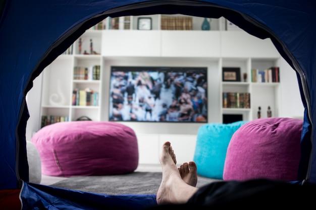 私は家のテントの中でテレビを見て座っています。