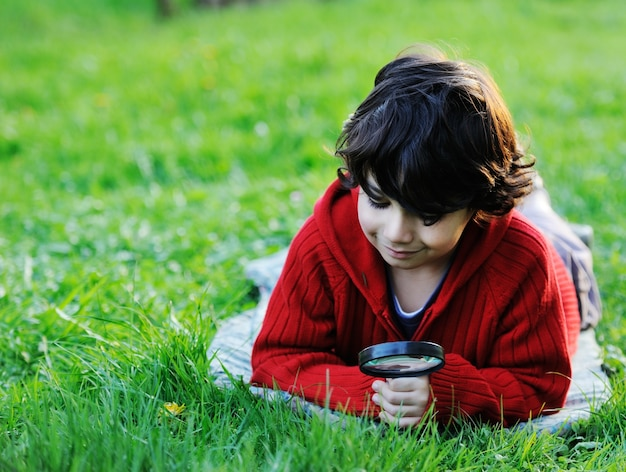 幸せな子供が虫眼鏡で自然を探索する