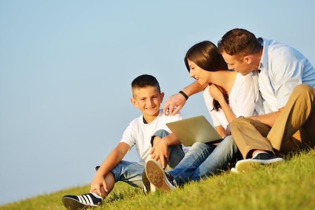 Счастливая семья на красивый летний луг, имеющие счастливое время с ноутбуком