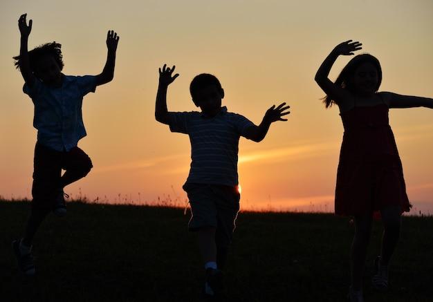 日没時の自然の中の幸せな人々のシルエット