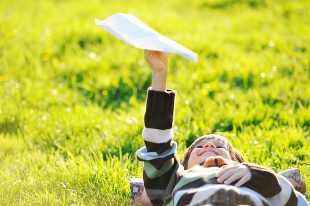 Счастливый ребенок, наслаждаясь солнечный конце лета и осенний день в природе на зеленой траве