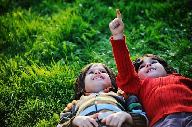 晴れた夏、秋の日、緑の草の上で自然を楽しむ幸せな子供