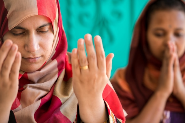 一緒に祈るイスラム教徒とキリスト教の女性