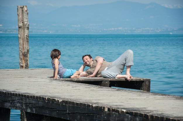 父、息子、海のドックで夏休みを楽しむ