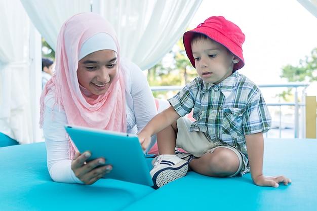 夏休みに幸せなイスラム教徒の若い女性と小さな男の子