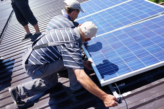 Человек, устанавливающий фотоэлектрические солнечные панели на солнечной энергии