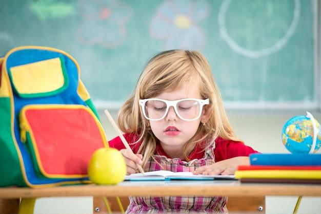 学校の教室でかわいい小さな学校のブロンドの女の子が座って