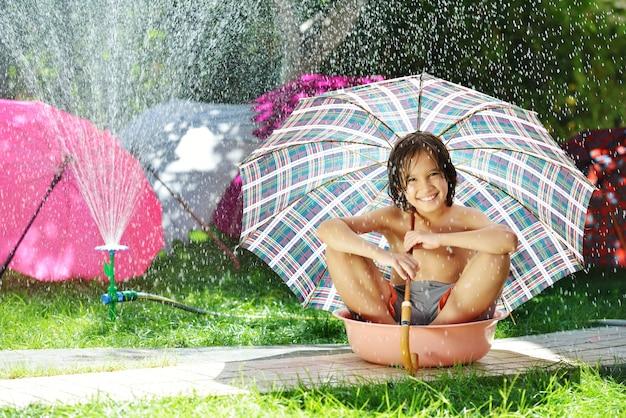 Дети играют с спринклерной водой, держа зонтик на летнем заднем дворе