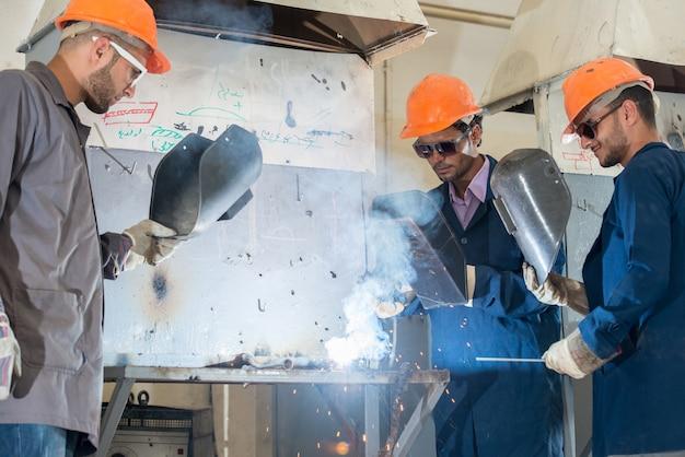 Работник с защитной масляной сваркой металла на заводе