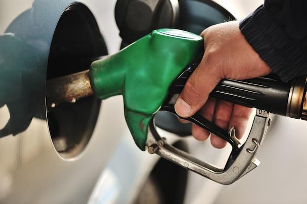 Крупным планом изображение мужской руки, заправляющей автомобиль газовым насосом