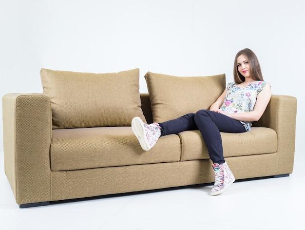 白い部屋の現代的なソファに座る