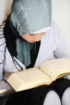 コランを読んでいるイスラム教徒の子供
