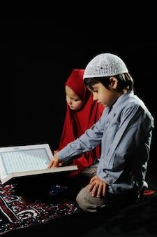 黒の背景に神聖なコーランを読むムスリムの子供たち