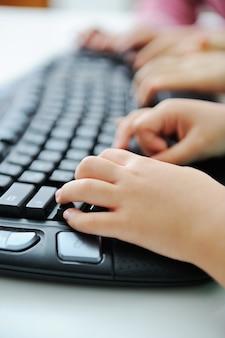 子供の手がキーボードで入力する