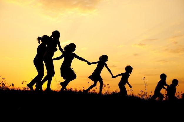 シルエット、草原で遊んでいる幸せな子供たちのグループ、日没、夏期