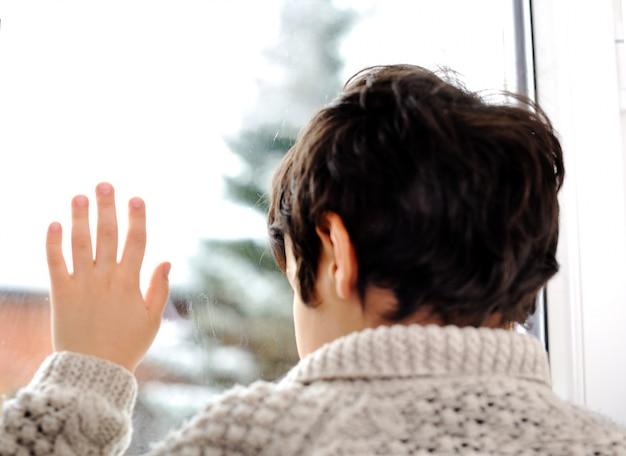 窓と冬の雪に悲しい子供は外です
