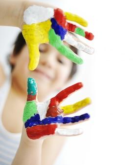 手のプリントのための準備がカラフルなペイントで描かれた手の小さな男の子