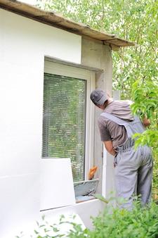 Строитель, применяющий изоляцию над внешней стеной дома
