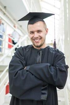 Молодой студент-мужчина в черном выпускном платье
