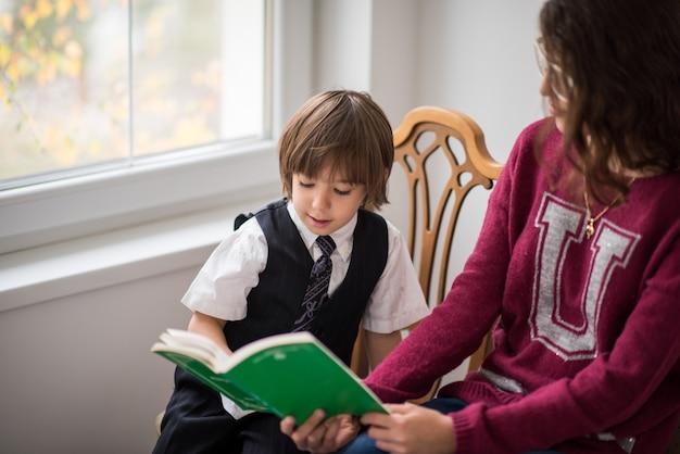 椅子の読書に本を持つスマートかわいい男の子