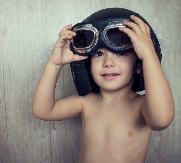 Счастливый игривый мальчик с летающим шлемом